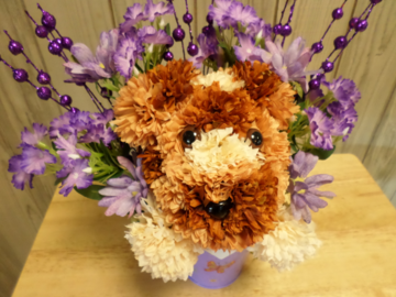 A fun puppy bouquet made out of silk flowers
