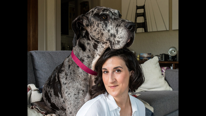 Great Dane resting her head on her owner's head