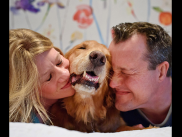 Golden retriever snuggling cheek to cheek with owners