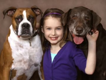 A portrait of  a girl and her two dogs.
