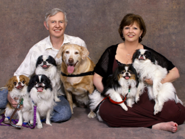 A portrait of a couple with their six dogs