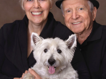 A portrait of a couple with their dog