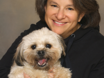 A portrait of a woman hugging her dog