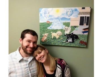 "Happy couple with their 18x24"" memorial painting of 4 dogs they dearly loved."