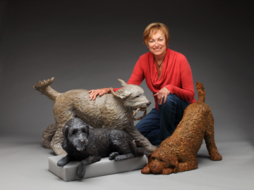 The artist with three labradoodle bronze portraits