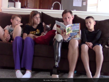 Wounded Warrior Ben reading Pink's book to his children, Pink and Toaster on couch!