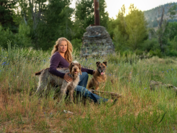 Woman with two dogs in field