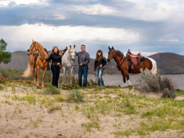 Family with horses by lake